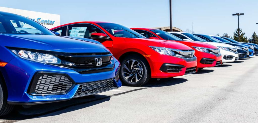 New Honda Civic lined up in a dealership parking lot with different colours