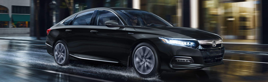 3/4 view of a 2019 Honda Accord Hybrid driving on wet roads