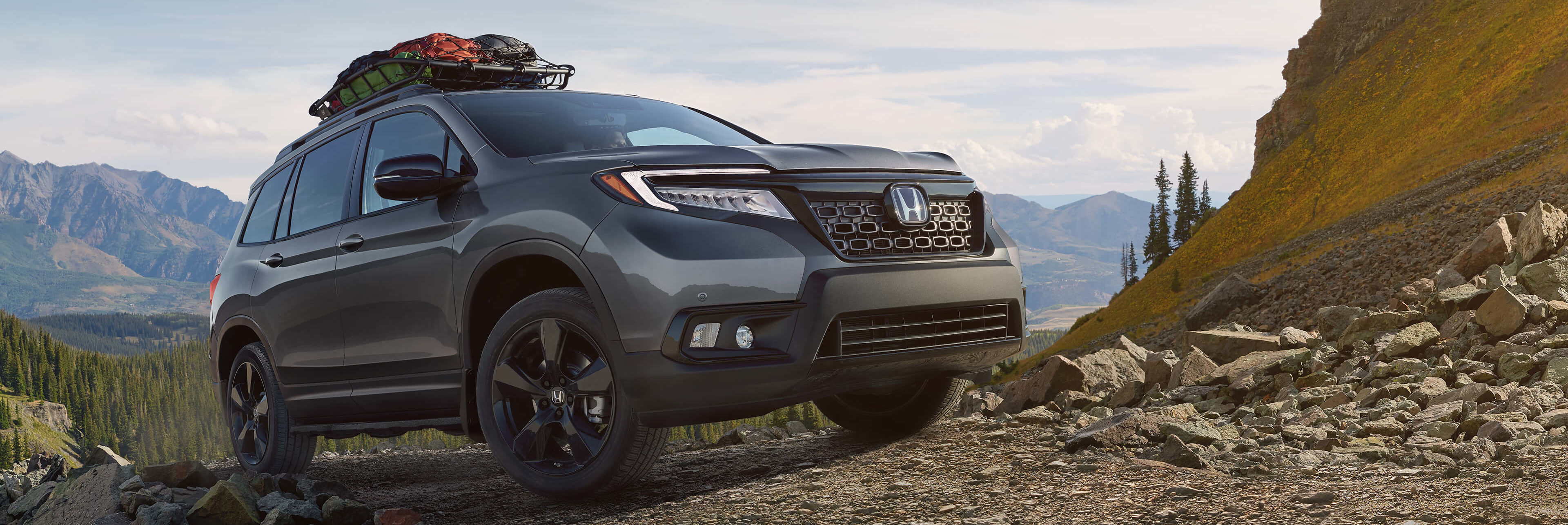 Honda Passport driving over a rocky hill with cargo on top