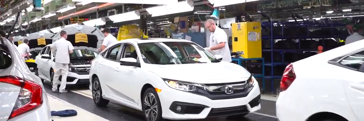 Line of white Honda civics getting inspected in a plant