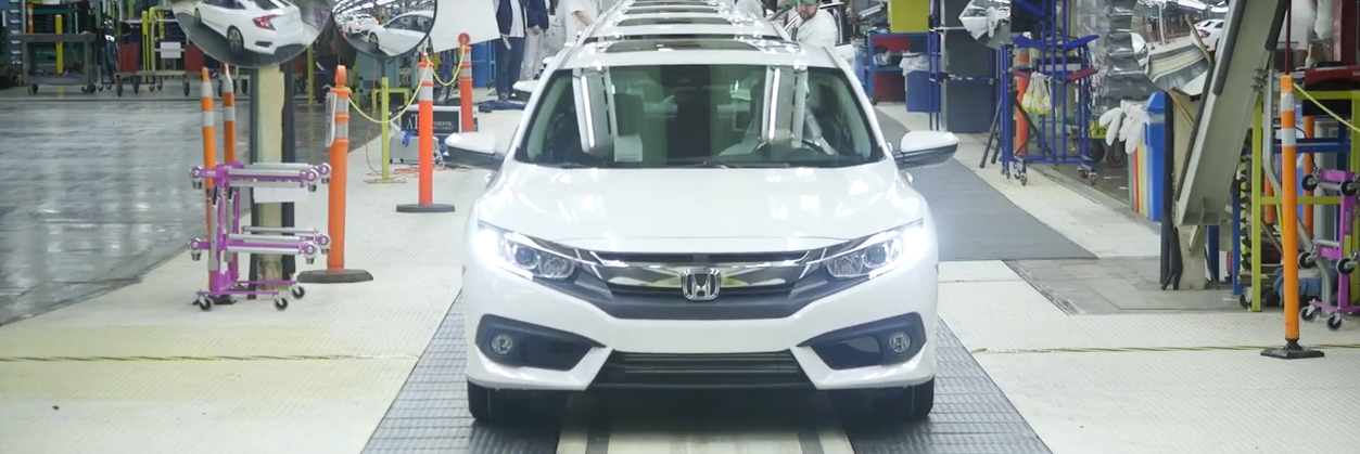 Front of white Honda in a plant