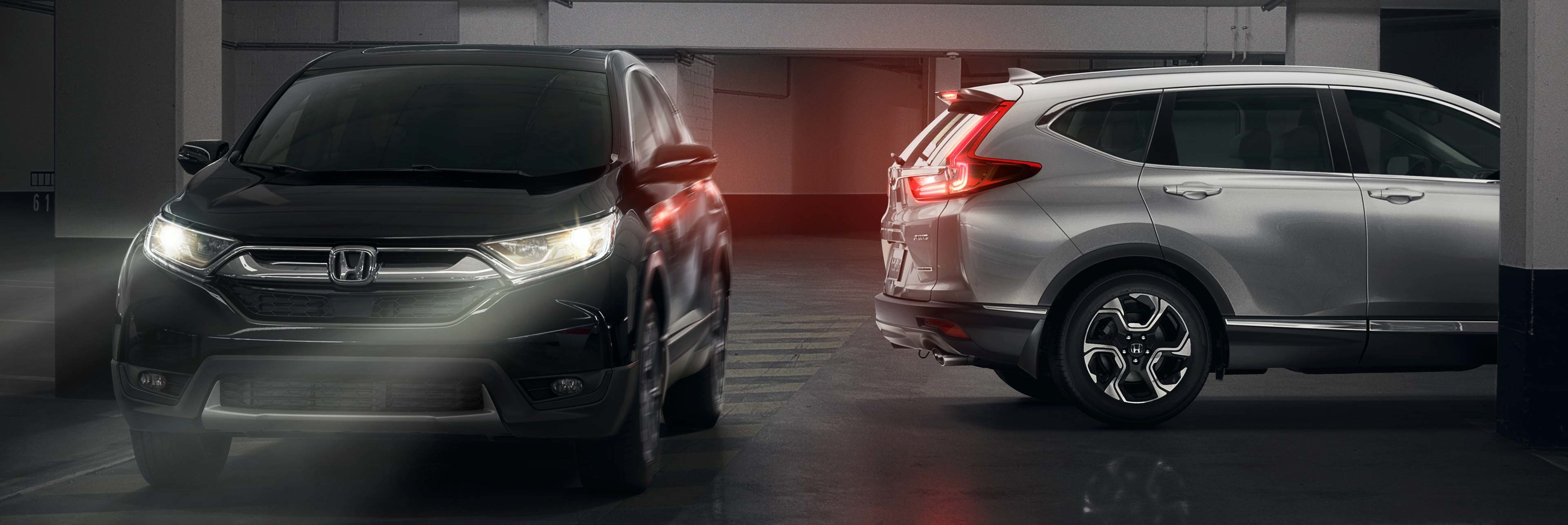 CR-V in parkade with lights on next to side rear profile of another CR-V