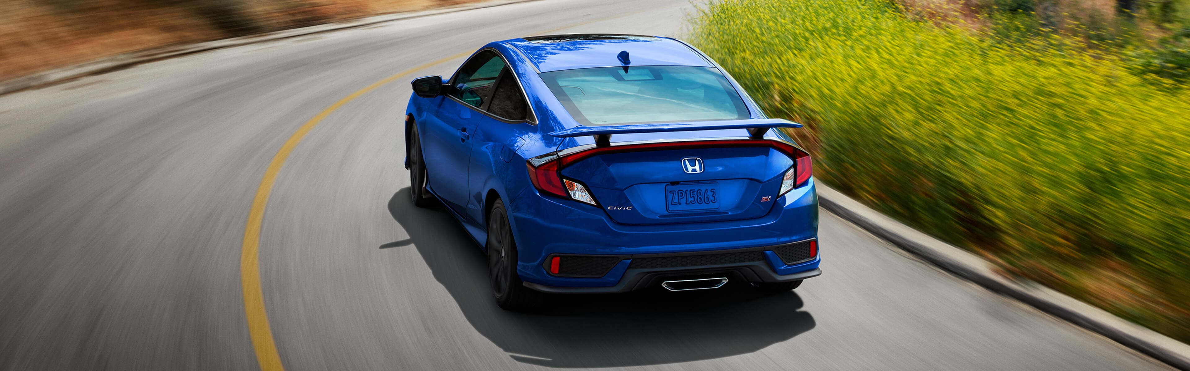 Rear of Honda Civic Coupe driving in the country
