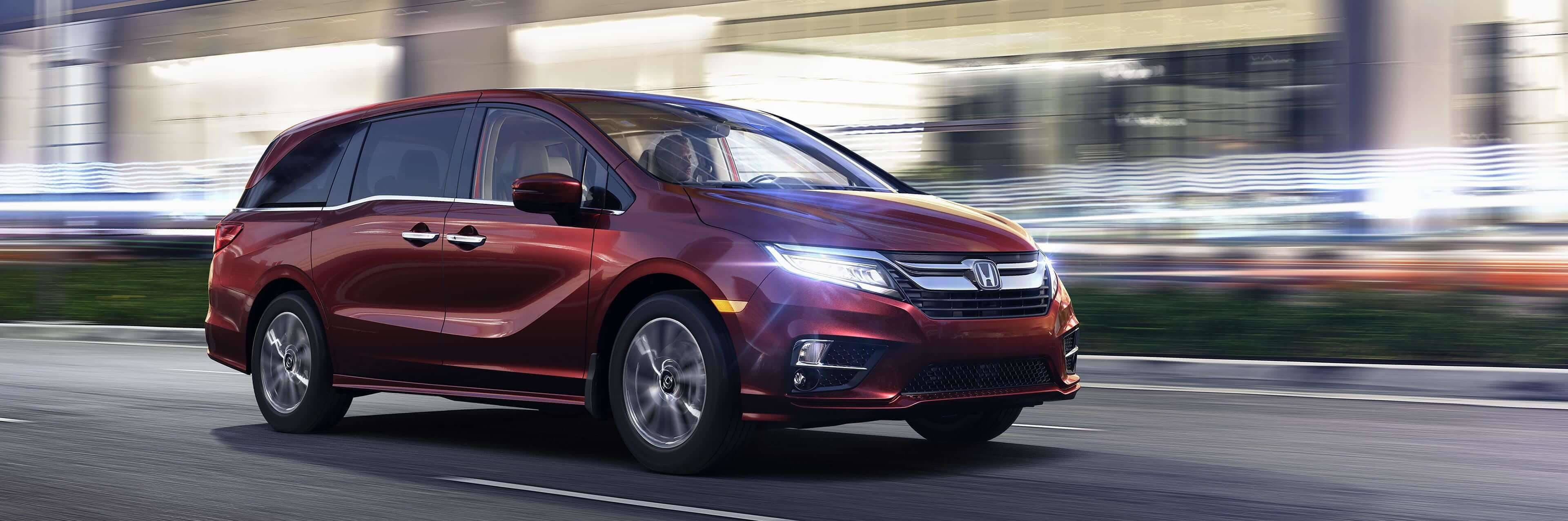 2020 Honda Odyssey shown in red driving on a late night city street