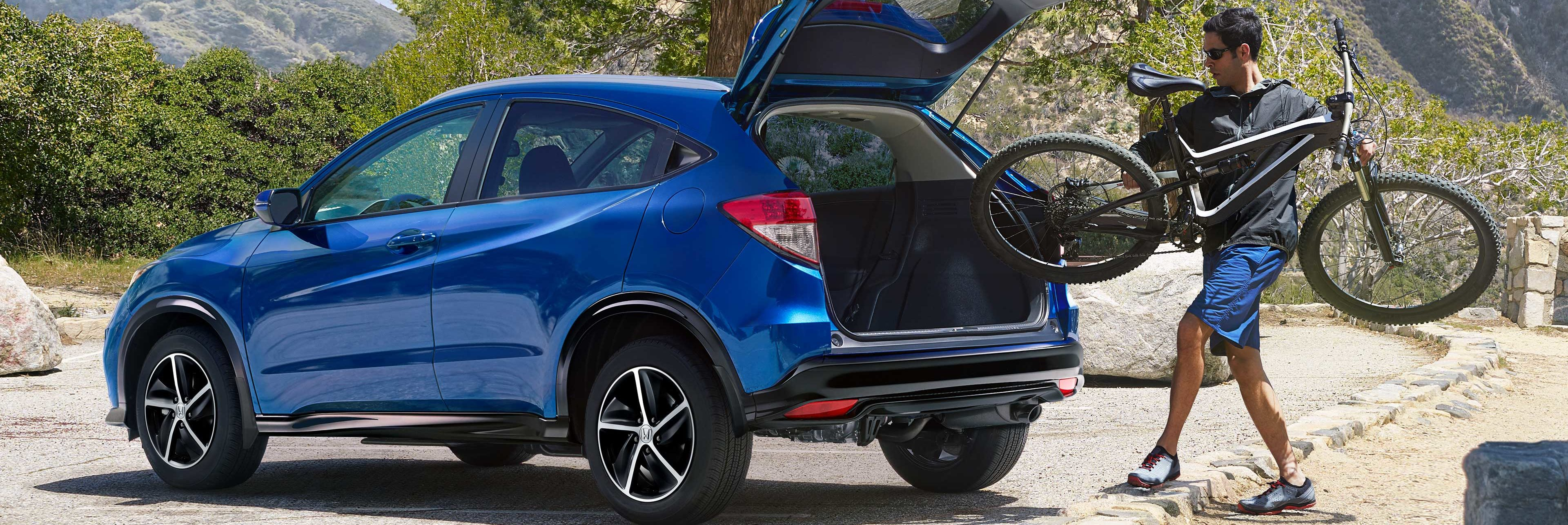 Shot of man placing bicycle into the back of a 2020 HR-V shown in blue