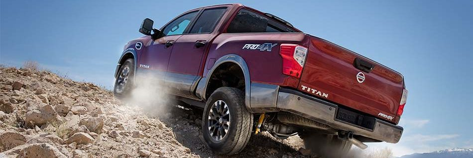 2018 Nissan Titan driving up a rocky hill