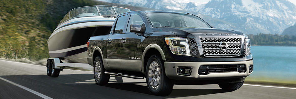 Nissan Titan pulling a boat behind it while driving by a lake and mountains
