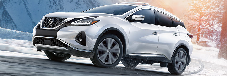 Nissan Murano parked on the snow in front of mountains