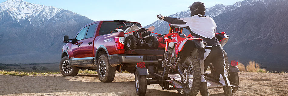 A quad in the box of a Nissan Titan with someone pushing a dirtbike onto a trailer behind the truck