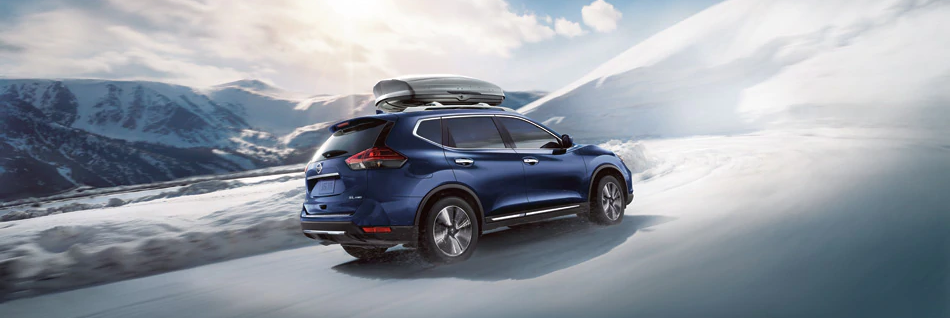 2020 Blue Nissan Rogue driving in the snow