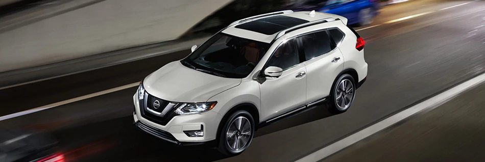 2020 White Nissan Rogue from the top driving down a city road