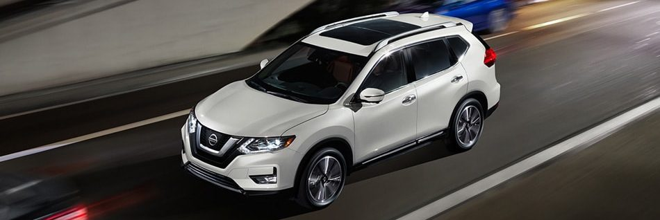 White 2020 Nissan Rogue driving down city road