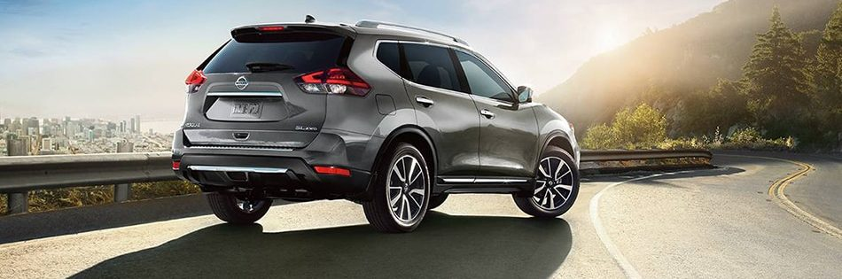 2020 Nissan Rogue SL AWD shown in Gun Metallic, parked on sunny highway, city in background