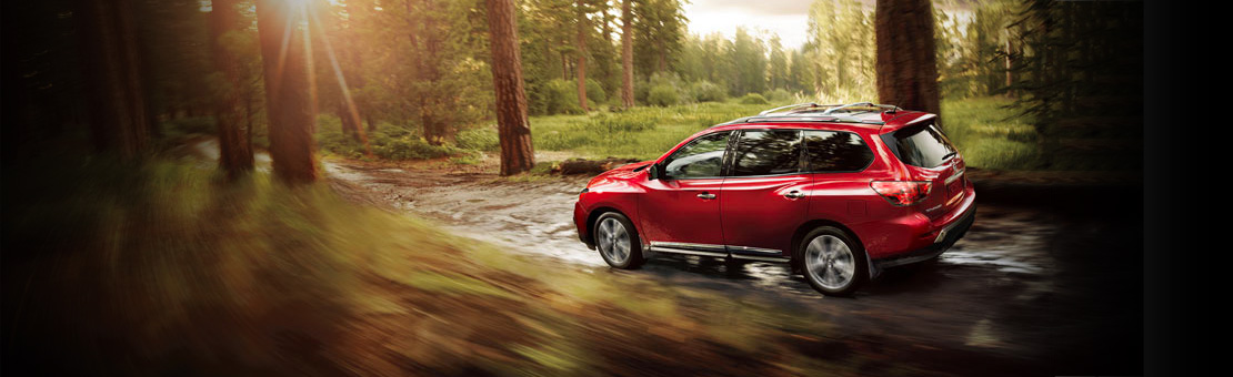 Nissan Pathfinder driving through a forest
