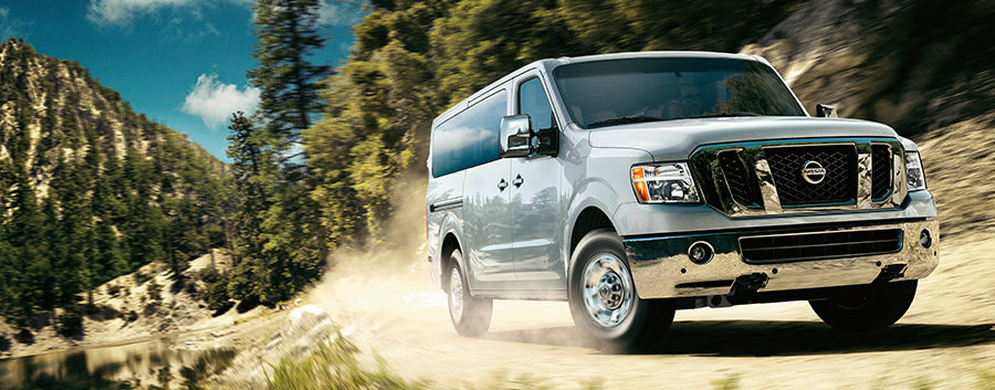 2020 nissan nv passenger van driving through the woods on a dirt road by body of water