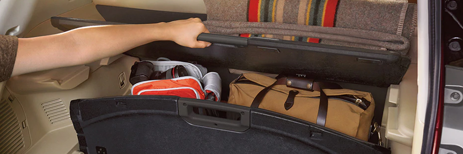 Nissan Divide-N-Hide partition storage, storing a brown bag and a white and orange backpack while a rolled-up blanket is positioned on the top shelving unit