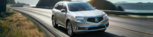 Silver 2018 Acura MDX driving on a highway by water