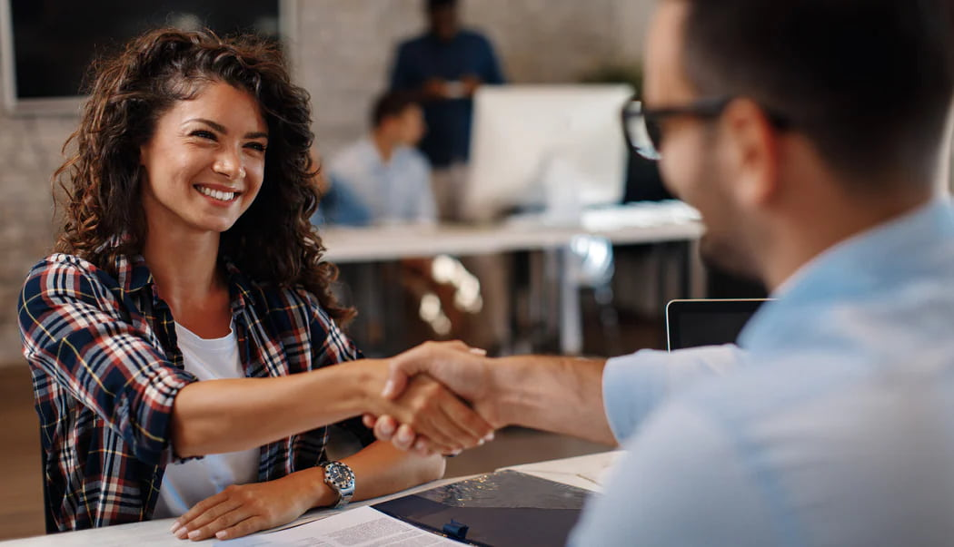 A woman shaking hands with a sales associate agreeing to a contract