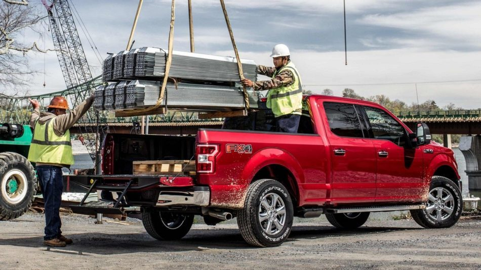 Two men in yellow vests and hard hats load a bundle of steel girders into the bed of a red Ford F-150 at a busy work site