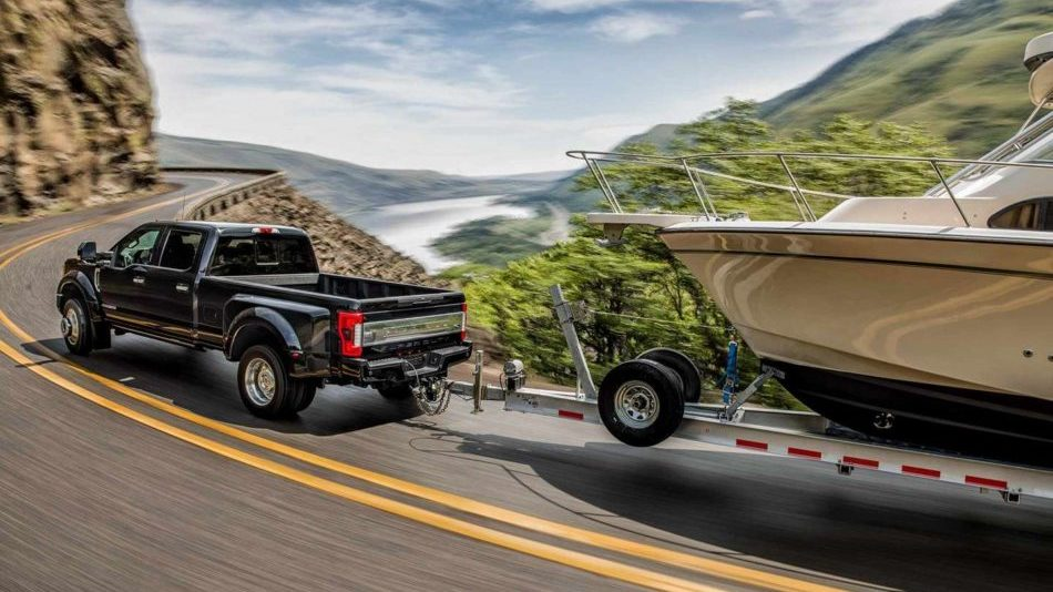 A Ford Super Duty tows a boat around a mountain road along the coast