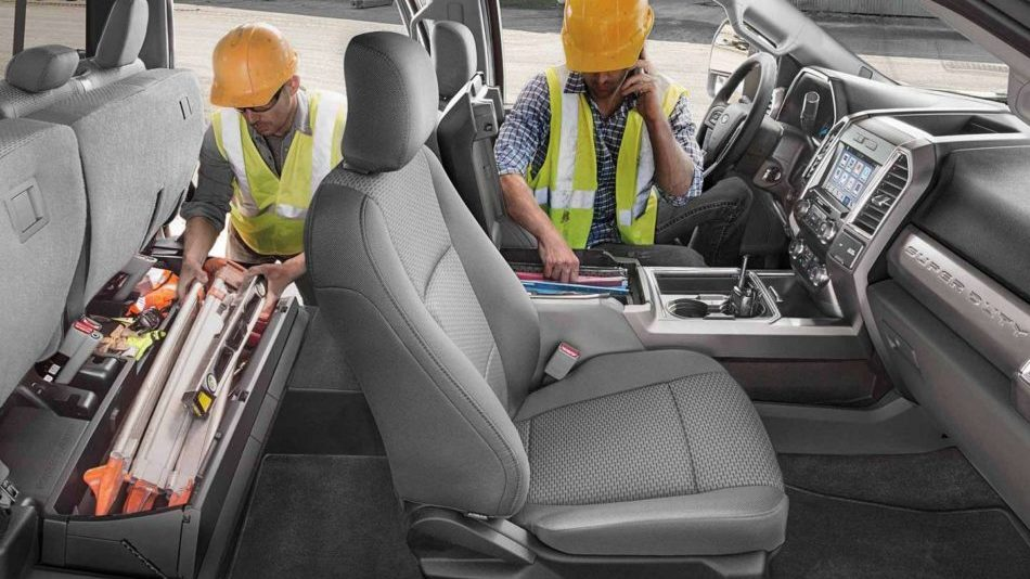 Two men in yellow vests and orange hard hats make use of the spacious interior of the Ford Super Duty, loading in tools into the under-seat storage
