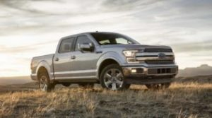 A silver Ford F-150 parked on a prairie at dusk