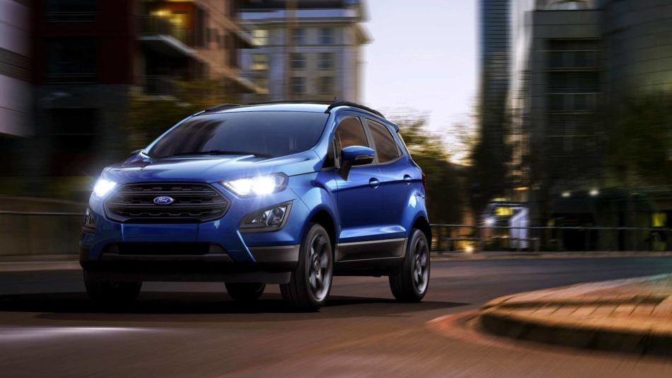 A blue Ford EcoSport, headlights on, drives around a corner on a city street at dusk