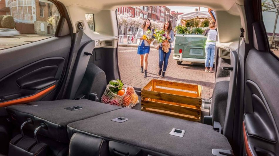 Looking out of the back of a Ford EcoSport, with the rear seats folded down, at two women who are loading groceries on a sunny day