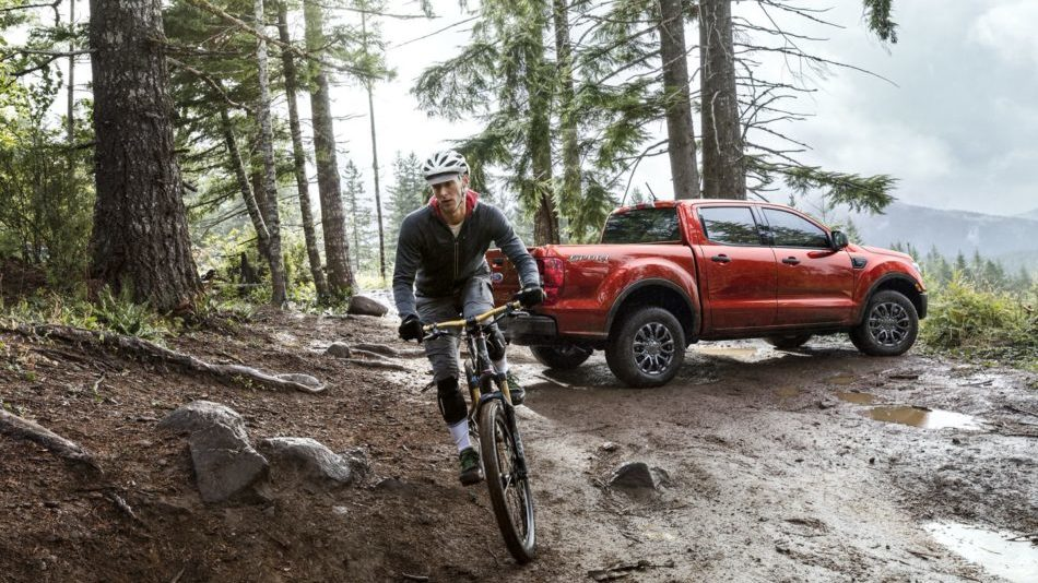 A red Ford Ranger parked in a misty forest in the mountains, while a man bikes away on his mountain bike