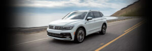 Front 3/4 view of the 2021 Volkswagen Tiguan driving across a mountain pass with the ocean next to it